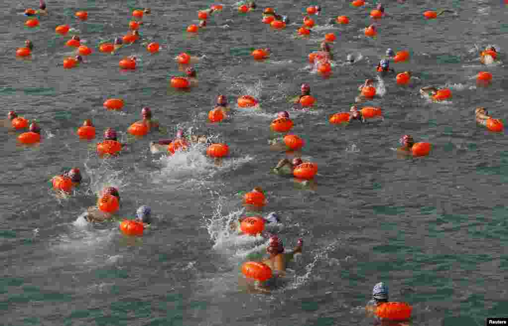 Swimmers, with buoys attached, compete in a cross harbor swimming event at Hong Kong's Victoria Harbour.