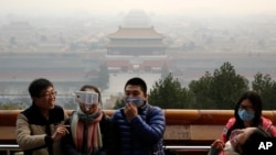 FILE - Visitors, some wearing masks to protect themselves from pollutants, share a light moment as they take a selfie at the Jingshan Park on a polluted day in Beijing, Monday, Dec. 7, 2015.