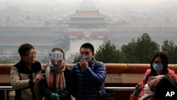 2015年12月7日一些游客在北京的雾霾天到景山公园拍照。