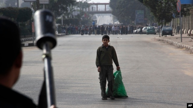 A boy looks at Egypt's security forces as they try to disperse supporters of ousted President Mohamed Morsi in Cairo, Egypt, Friday, Jan. 17, 2014.