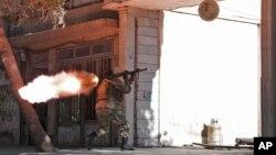 Một binh sĩ Afghanistan nhắm bắn về đang diễn ra cuộc giao tranh giữa các phần tử nổi dậy và lực lượng an ninh tại Lãnh sự quán Ấn Độ ở Afghanistan, 23/5/14