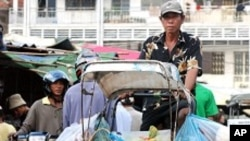 A cyclo driver ferries goods to Psar Kandal market in Phnom Penh.