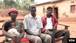 Silas Bihizi, center, sits with Valens Rukiriza, right, Rukiza's wife and one of their grandchildren outside the Rukiza family home in Buguli, Rwanda.