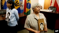 Raida Condor, right, and Carmen Amaro, relatives of Amador Condor, killed during the government of Peru's former President Alberto Fujimori, hold a portrait of him, inside the chambers of the Inter-American Court of Human Rights where judges are analyzing arguments against a presidential pardon of Peru's former President Alberto Fujimori, in San Jose, Costa Rica, Feb. 2, 2018.