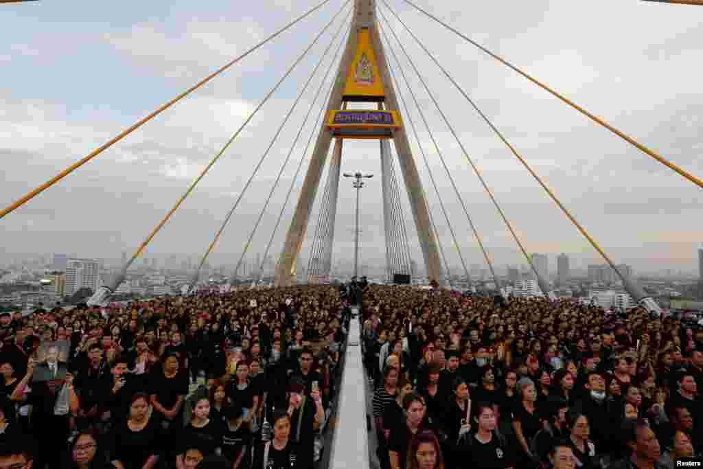 ប្រជាជនប្រមូលផ្តុំគ្នានៅលើស្ពាន Bhumibol Bridge ពីលើទន្លេចៅប្រះយ៉ាក្នុងក្រុងបាងកក ប្រទេសថៃ ដើម្បីប្រារព្ធពិធីបុណ្យចម្រើនព្រះជន្មអតីតព្រះមហាក្សត្រព្រះបាទ Bhumibol Adulyadej។