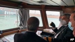 In this photo released by the Suez Canal Authority, Lt. Gen. Ossama Rabei, head of the Suez Canal Authority, second right, speaks to other staff onboard a boat near the stuck cargo ship Ever Given on Wednesday, March 24, 2021.