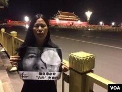广东维权人士李小玲6月3日晚到北京天安门举牌 (参与网图片)