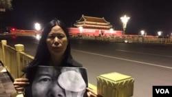 """广东维权人士李小玲6月3日晚到北京天安门举牌,牌上写""""光明六四,光明行"""",并燃点蜡烛。 (参与网图片)。后来李小玲等人以""""涉嫌寻衅滋事""""为由被刑拘。"""