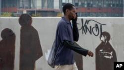 Un homme se couvre le nez et la bouche dans le centre-ville de Johannesbourg, Afrique du Sud, le 16 mars 2020.