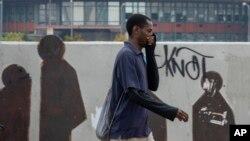 Seorang pria menggunakan tangan untuk menutup mulut dan hidung saat berjalan di Johannesburg, Afrika Selatan, Senin, 16 Maret 2020. (Foto: AP)