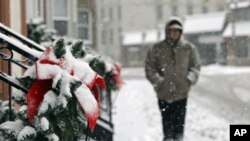 A man walks past snow-covered Christmas decorations on apartments in Berea, Ohio, December 26, 2012. (AP Photo/Mark Duncan)