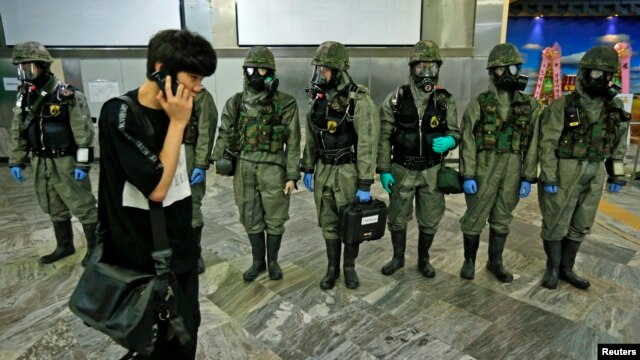 A man using his phone walks past South Korean soldiers wearing protective gears during an anti-biochemical terrorism exercise at a subway station in Seoul, May 7, 2013.