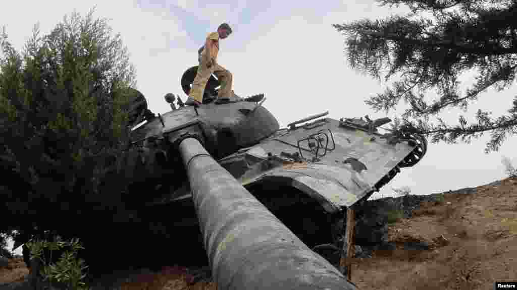 A boy walks on a damaged Syrian Army tank, belonging to forces loyal to Syria's President Bashar al-Assad, near Idlib October 2, 2012.