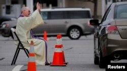 На парковці біля Католицької церкви Святої Марії отець приймає сповіді з автомобілю, Массачусетс, 1 квітня 2020 (REUTERS/Brian Snyder)