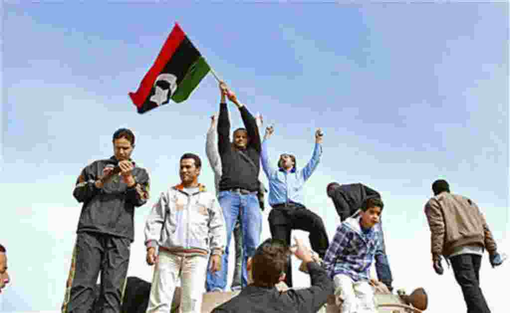 Un grupo levanta una bandera de la era pre-Gadafi en Bengazhi, Libia.