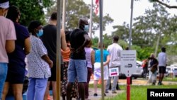 Ljudi čekaju u redu ispred biblioteke u Miamiju tokom ranog glasanja, 19. oktobra 2020.