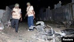 Somali police officers assess the scene of an explosion outside the Jazira hotel in Mogadishu, Jan. 1, 2014.