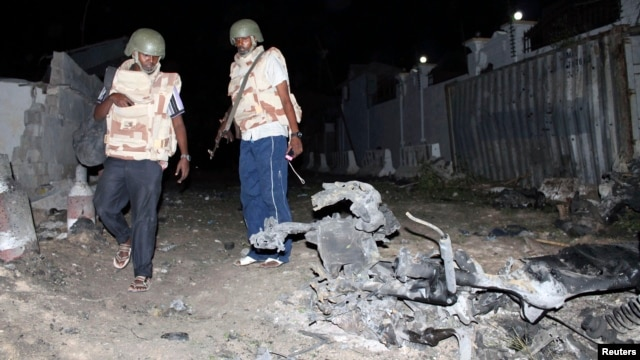 Somali police officers assess the scene of an explosion outside the Jazira hotel in Mogadishu, Jan. 1, 2014.