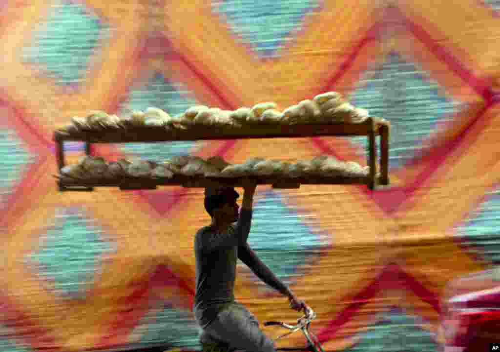 A vendor carries a bread tray while riding a bicycle, in Cairo, Egypt.