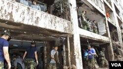 Tentara Korea Selatan membersihkan apartemen di Seoul yang rusak akibat dihantam lumpur longsor (28/7).