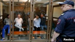 Defendants in the murder trial of Russian investigative journalist Anna Politkovskaya are seen inside a glass-walled cage, with a policeman standing guard in the foreground, during a court hearing in Moscow, June 9, 2014.