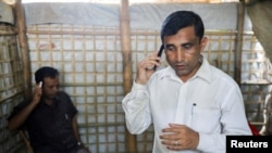 FILE - Mohib Ullah, a Rohingya Muslim leader from the Arakan Rohingya Society for Peace and Human Rights, speaks on a phone at his residence in Kutupalong refugee camp in Ukhiya, Cox's Bazar, Bangladesh, April 21, 2018.