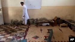 Seorang murid berjalan di sebuah kelas pasca ledakan di sekolah yang terletak di Karachi, Pakistan (28/4). Tiga siswa dilaporkan tewas dalam insiden tersebut.