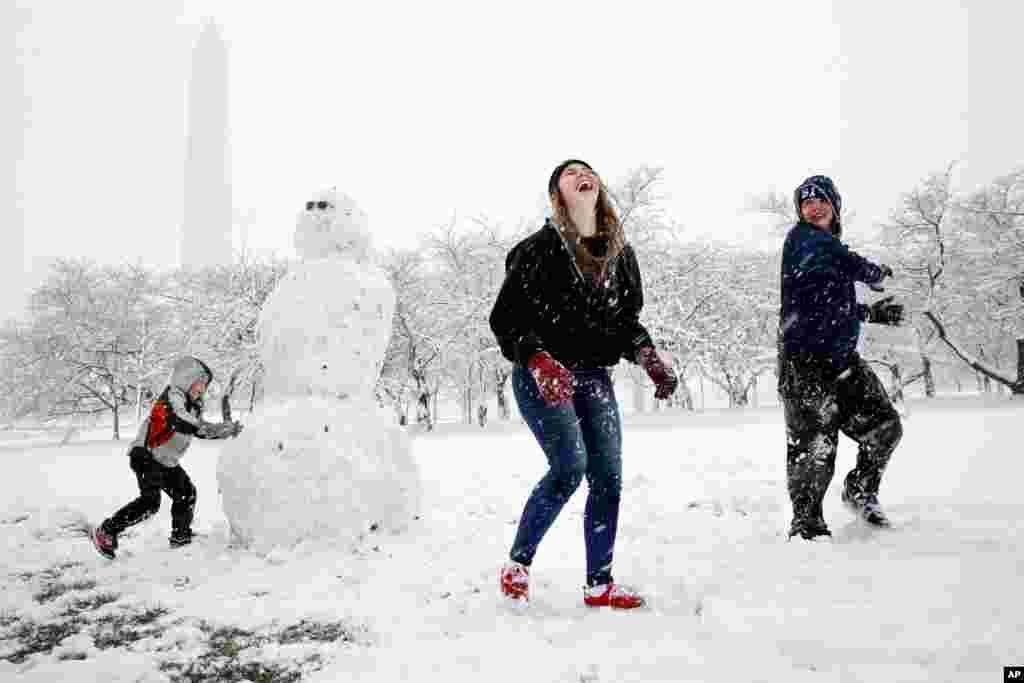 Des enfants s'amuse dans la neige à Washington, lors d'une tempête de neige, le 21 mars 2018.