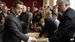Presiden Perancis dan kandidat UMP Nicolas Sarkozy (kiri) memasukkan surat suaranya ke kotak di salah satu TPS di Paris (6/5).