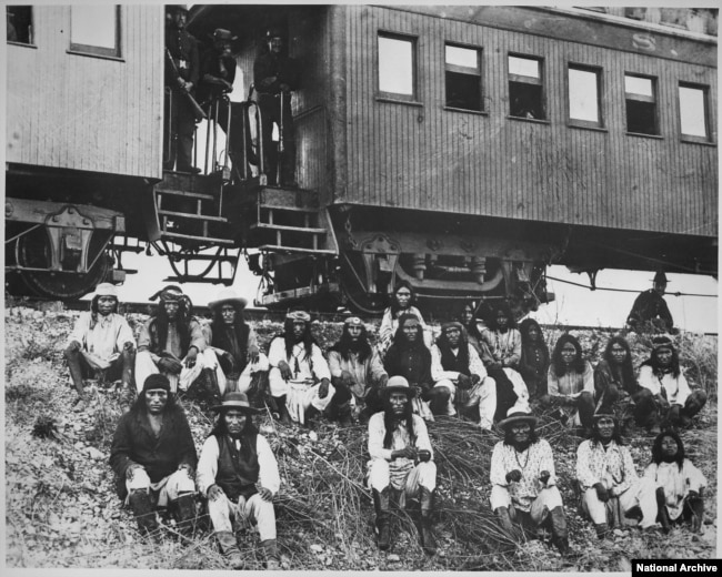 Geronimo (front row, third from right) and his Chiricahua followers as prisoners of war en route to Florida, 1886.