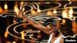 """Lupita Nyong'o, aktris pendukung terbaik Oscar 2014 dalam film """"12 Years a Slave"""" saat memberikan sambutan di panggung Academy Awards ke-86 di Hollywood, California (2/3)."""