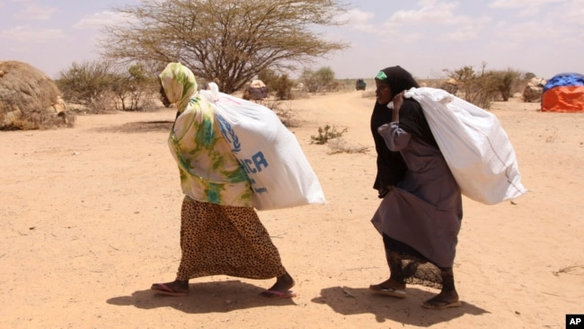 FILE - Southern Somali women carry food aid donations from the UNHCR as they make their way to their refugee camp in Dollow, Somalia, Aug. 30, 2011. Hunger is again stalking the country, and the U.N. is appealing for aid.