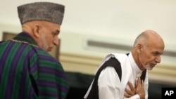 Ashraf Ghani, kanan, dan Presiden Hamid Karzai, kiri, di Kabul, 21 September 2014.