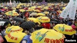 2019年6月9日在中國香港,示威群眾要求當局廢除擬議中的把犯人引渡到中國的法案。他們手持黃色遮陽傘,這是過去的佔領中環運動的象徵。