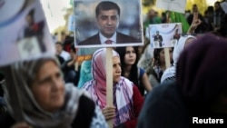 A Kurdish woman living in Athens, Greece, holds a photo of arrested HDP co-leader Selahattin Demirtas, during a demonstration against the Turkish government following the arrests of pro-Kurdish officials in Turkey, Nov. 5, 2016.
