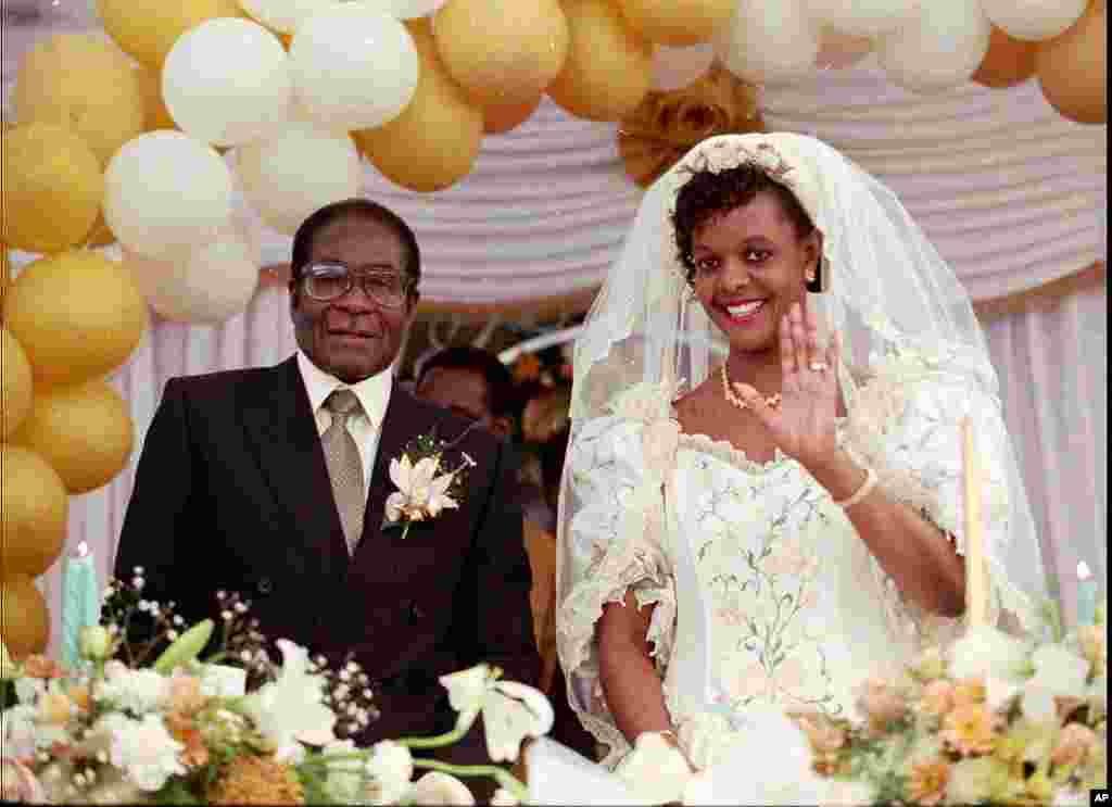 Grace Marufu, 31, the new bride of Zimbabwean President Robert Mugabe, 72, right, waves at guests after their wedding ceremony at the Kutama catholic mission, west of Harare, August 17, 1996. (AP)