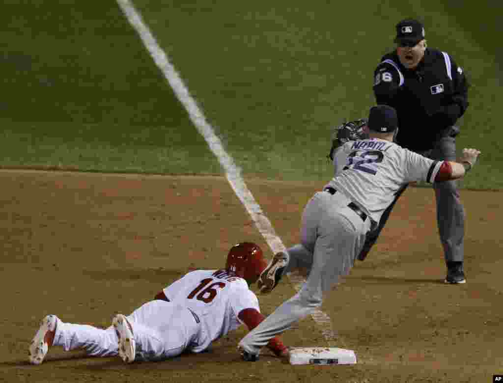 St. Louis Cardinals' Kolten Wong is out at first base as Boston Red Sox first baseman Mike Napoli takes the pick off throw to end Game 4 of baseball's World Series against the St. Louis Cardinals, Oct. 27, 2013, in St. Louis. The Red Sox defeated the Cardinals 4-2.