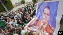 在卡扎菲丧生儿子的丧礼中政府组织的人群高举被北约空袭炸死的一名上校的图像