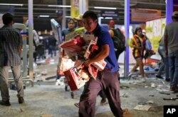 A man runs with toys as a store is ransacked by a crowd in the port of Veracruz, Mexico, Jan. 4, 2017.