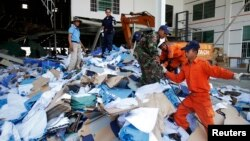 Rescue workers and soldiers search through a site of the accident in a shoe factory in the Kong Pisei district of Kampong Speu province, 50 km (30 miles) west of the capital, Phnom Penh, May 16, 2013.