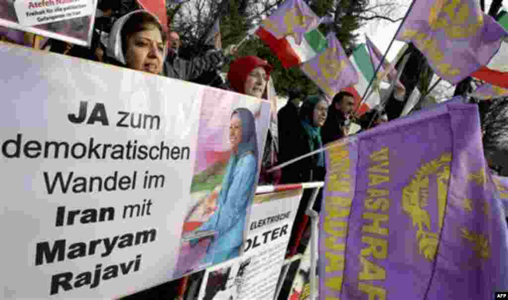 """Activists of the Iranian Resistance Council shout slogans against the government in Iran during a demonstration in front of the Iranian embassy in Berlin, Germany, Tuesday, Feb. 15, 2011. Poster reads """"Yes to a democratic change in Iran with Maryam Rajavi"""