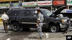 Iraqi security forces inspect the scene of a roadside bomb in central Baghdad, Iraq, 26 Sep 2010