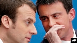 FILE - In this April 8, 2015 file photo, then French Prime Minister Manuel Valls, right, speaks with then Economy Minister Emmanuel Macron in Paris. Presidential hopeful Macron has won the backing of Valls.