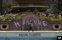 "Anti-government protesters begin gathering at Altamira Plaza, defaced with messages that read in Spanish; ""We're hungry. Maduro Dictator,"" in Caracas, Venezuela, June 26, 2017."