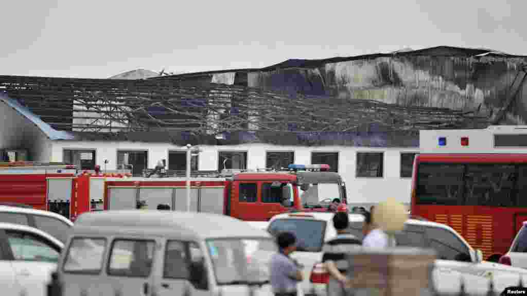 Rescue workers and fire trucks are seen outside a site of a fire, at a poultry slaughterhouse in Dehui, Jilin province, June 3, 2013.