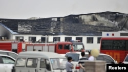 Para petugas penyelamat dan truk-truk pemadam kebakaran berada di rumah potong di kota Dehui, provinsi Jilin, China yang terbakar Senin (3/6).