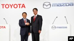 FILE - Toyota Motor Corp. President Akio Toyoda, left, and Mazda Motor Corp. President Masamichi Kogai pose for photographers before a press conference in Tokyo, May, 13, 2015. The Japanese automakers are partnering in electric vehicles with a deal expected to be announced Friday.