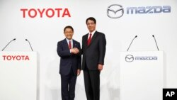 FILE - Toyota Motor Corp. President Akio Toyoda, left, and Mazda Motor Corp. President Masamichi Kogai pose for photographers before a press conference in Tokyo, May, 13, 2015. The Japanese automakers are partnering in electric vehicles with a deal expect