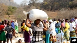 FILE: A woman decants palmoil distributed by the United Nations World Food Programme (WFP) in Mwenezi, about 450 kilometers (280 miles) south of Harare, Zimbabwe.