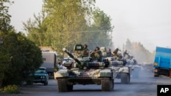 FILE - Azerbaijan tanks move toward Agdam, Azerbaijan, following days of escalated fighting between Azerbaijani and Armenian forces over a tense line of control around Nagorno-Karabakh, Aug. 2, 2014.
